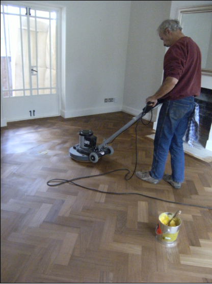 Ton, co-owner of Wood You Like - buffs in the solid wax to create the natural wear and tear layer on the Iroko parquet floor