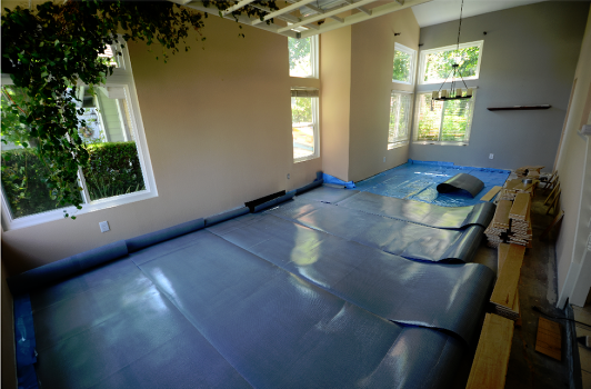 Rolls of Elastilon rolled out to start the installation of Maple Wood-Engineered flooring