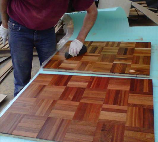 Ton of Wood You Like applying an oil finish to teak and mahogany mosaic boards